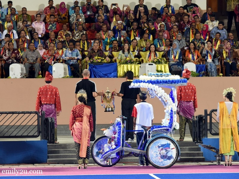 2. the Sultan Azlan Shah Cup is lifted by two hockey Olympians onto the grand stand
