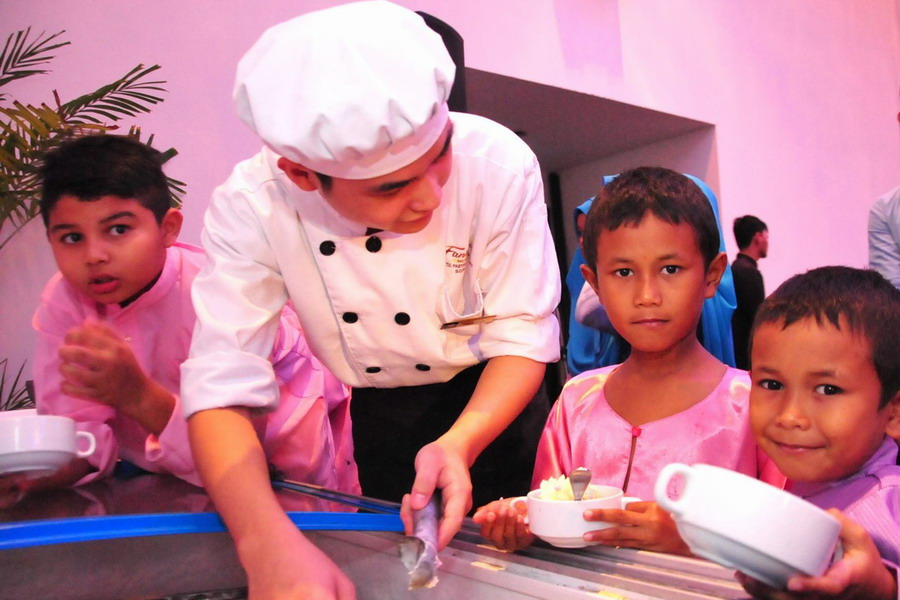 2. a F&B staff of Impiana Hotel Ipoh serves the children with ice cream