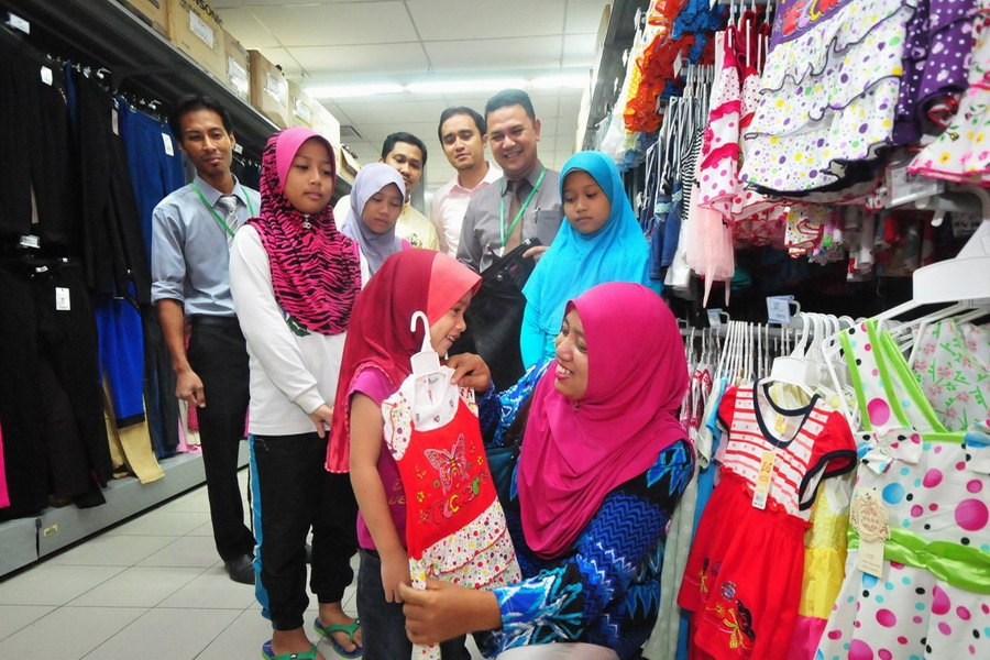 7. the children and their guardian choose new clothes for Hari Raya