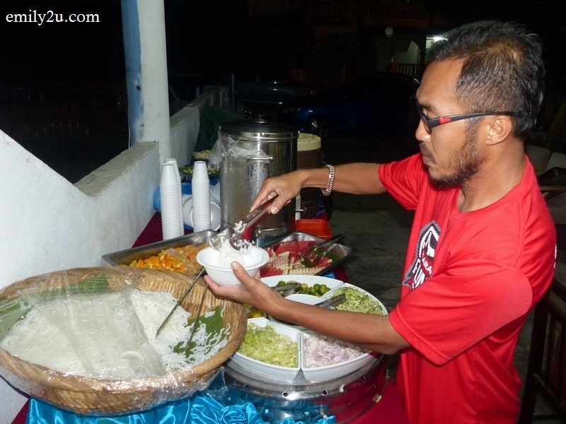 3. a guest helps himself to spicy laksa