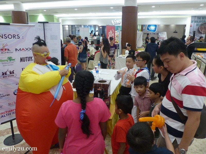1. Au Young in his sumo suit sculpts balloons for his fans