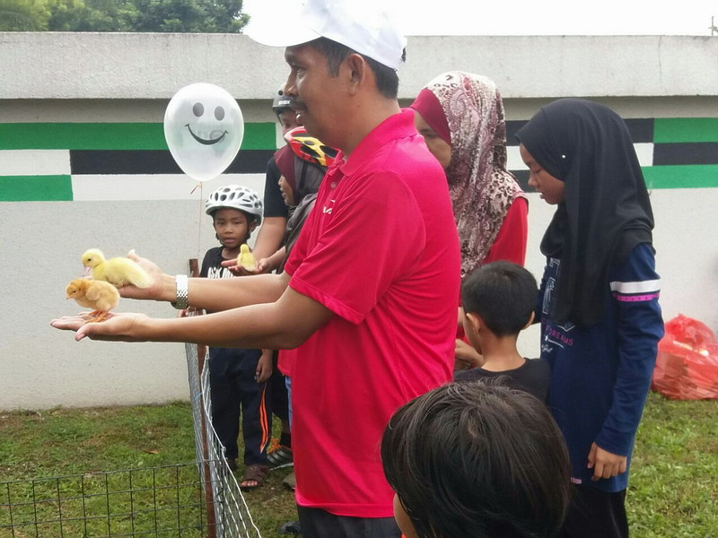 6. Ipoh City Mayor Dato' Zamri Man (in red) holds a pair of chicks at the mini petting zoo corner