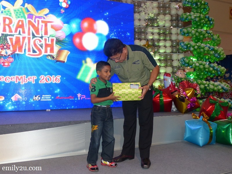4. this boy's smile tells it all as he receives a gift from Mr. Chan Yu Yin, Centre Manager for Ipoh Parade