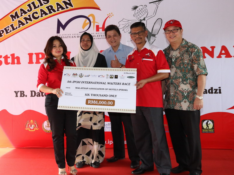 12. MAH Perak Chairperson Ms. Maggie Ong presents a mock cheque for RM6,000 to the 5th IIWR