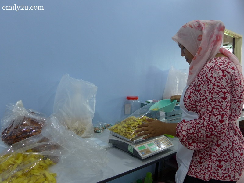 13. a worker packs all sorts of kacang putih snacks at the request of customers