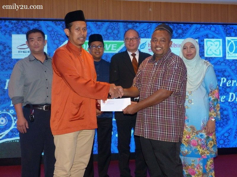 5. President of Kelab Sukan & Kebajikan Media Perak Wan Asrudi Wan Hasan (L) presents a cash donation on behalf of the media club to the person-in-charge of Pertubuhan Badan Kebajikan Anak-anak Yatim Darussalam