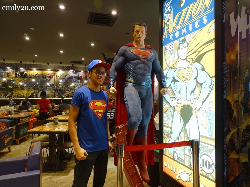 2. a server poses with a life-size Superman