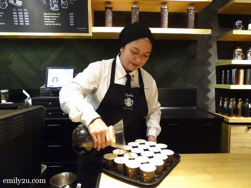 Ayesha pouring her brew into small cups for coffee tasting