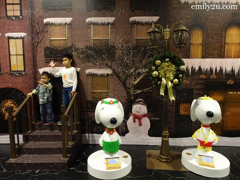 14. a snowy street scene with Snoopy in traditional costumes of Hawaii (L) and Palau (R)