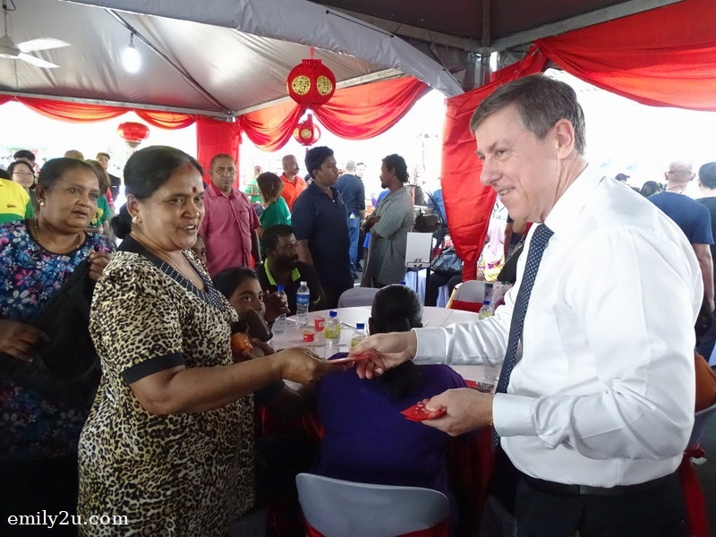 18. Dairy Farm Group's Group Chief Executive Officer Mr. Ian Mcleod (R) distributes angpow to recipients of MyKasih aid