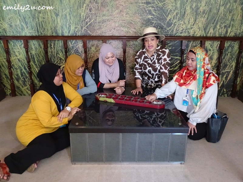 23. Maria Tunku Sabri (2nd from R) and friends play congkak