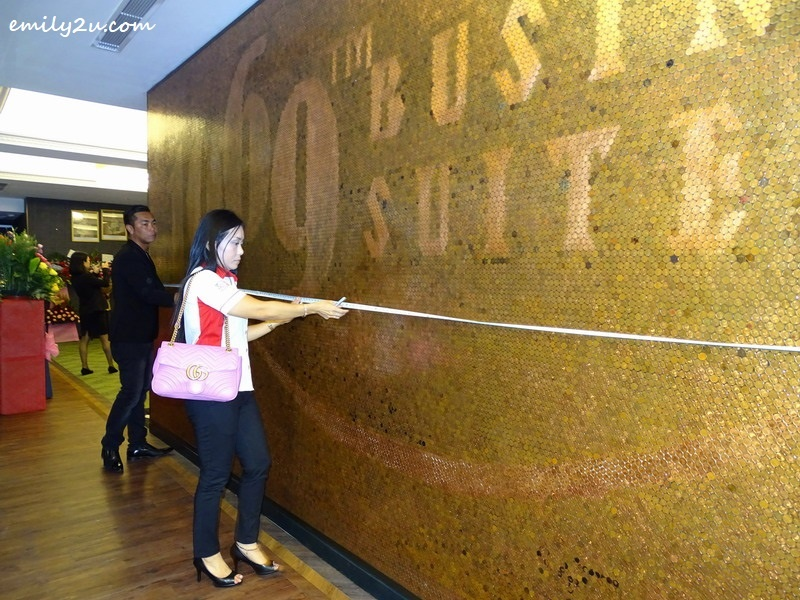 9. official from The Malaysia Book of Records, Ms. Lee Pooi Leng, measures the 1 sen coin mural