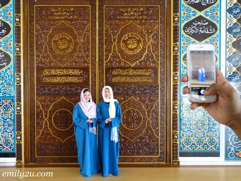3. visitors take a photo with the heavily carved door