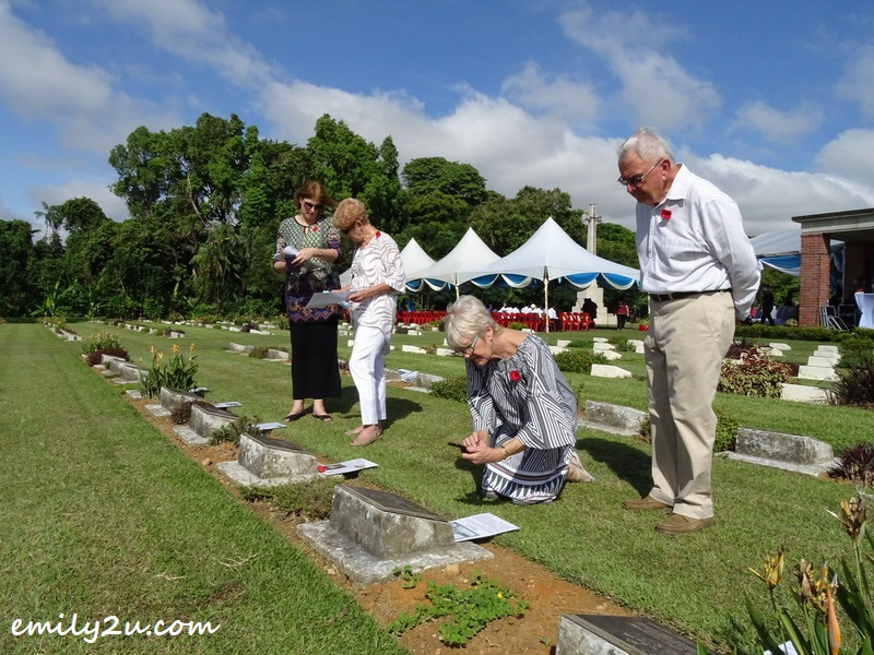 7. Wendy Currey (2nd from L) and half sister Teena (kneeling) visit the grave of Wendy's father, as well as five of his comrades from 93 Squadron RAAF, who were all killed in a horrific post-war take-off accident at Labuan Airfield