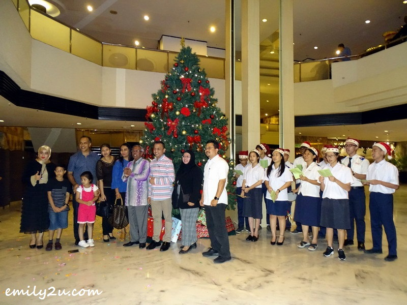 8. IHI staff Eza (L) and guests take a photo with the Christmas tree as backdrop