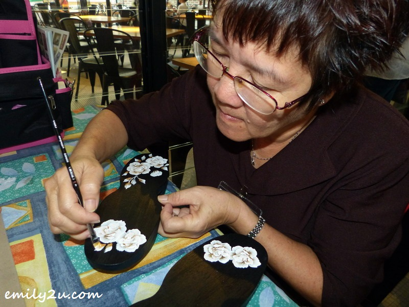 Foong KY doing one-stroke art on a pair of clogs