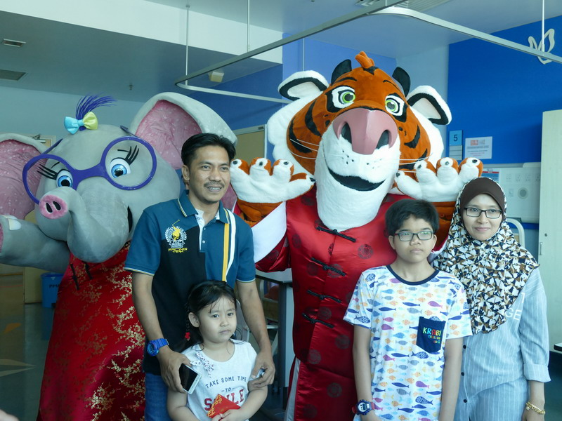 a family takes the chance to pose for a photograph with the mascots