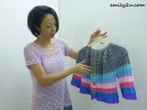 Samantha wearing a crocheted blouse, holding a multi-colored cardigan crocheted in cotton yarn sized for a 9-year-old girl