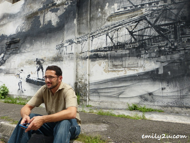 in front of evolution wall mural by Ernest Zacharevic