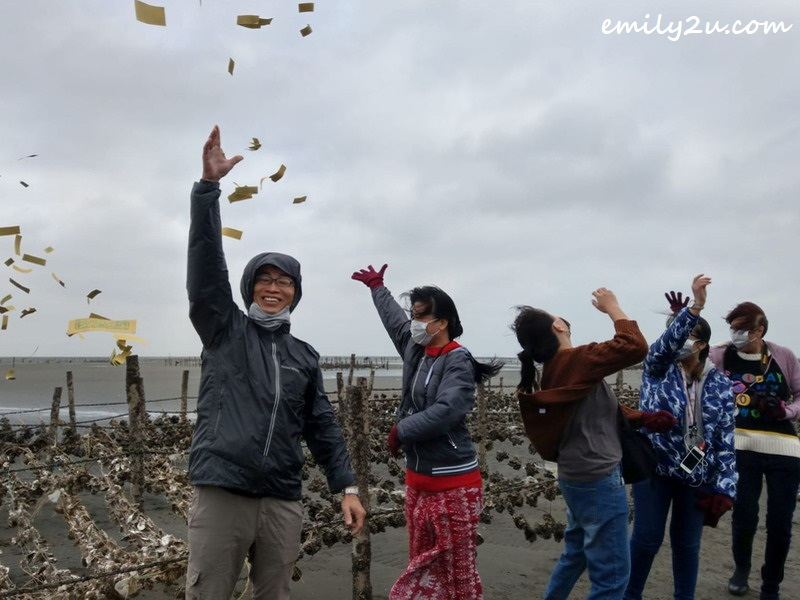 throwing joss paper into the air to appease sea spirits
