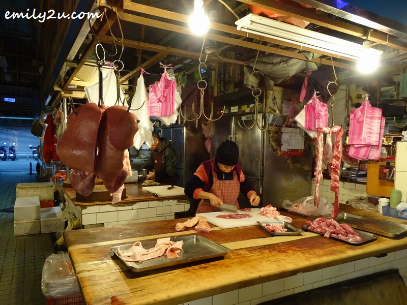 butcher prepares meat while waiting for customers