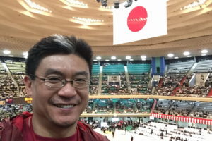 standing in front of the giant Japan flag that is the centrepice in the Nippon Budokan