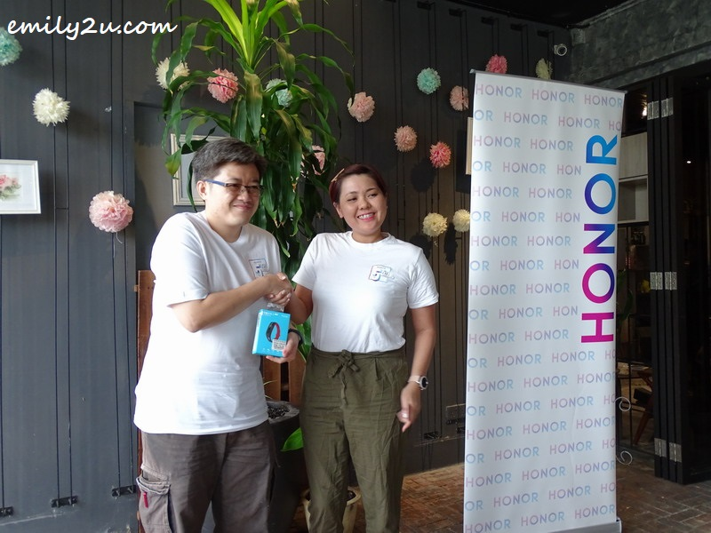 pioneer supporter, Ong Chee Meng (L), wins an Honor wearable device in the lucky draw