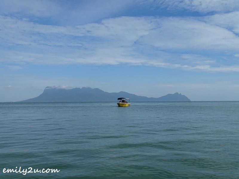 a boat with Mount Santubong as backdrop