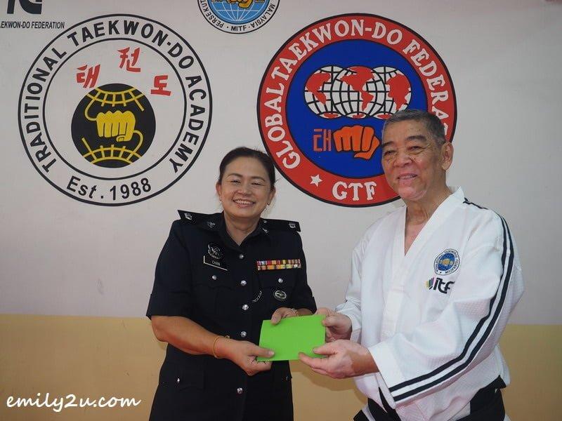 Grandmaster Yeow Cheng Watt presents a token of appreciation to DSP Chan Mei Ling