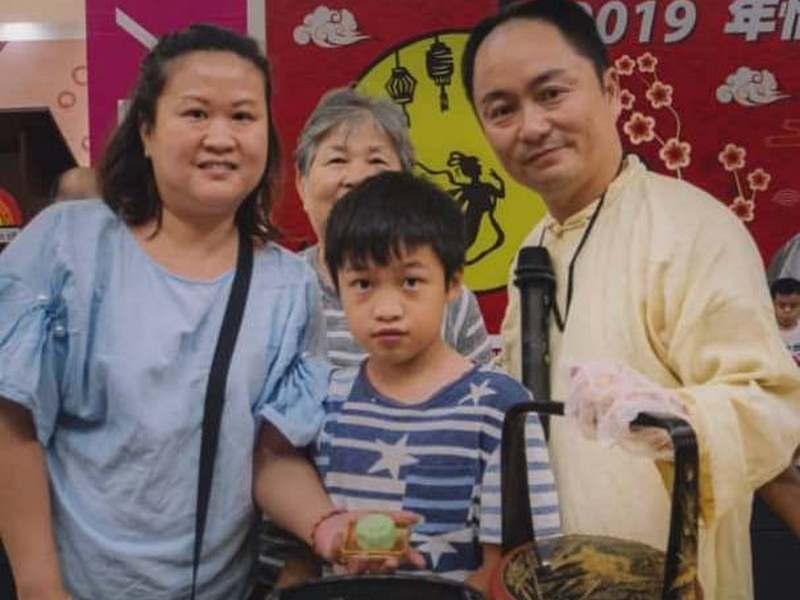 a family of three generations ready to make their own snow skin mooncakes, led by Au Young the instructor (R)