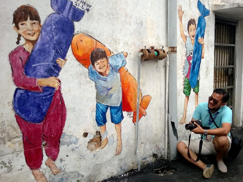 Eka photographs the wall mural in Ipoh
