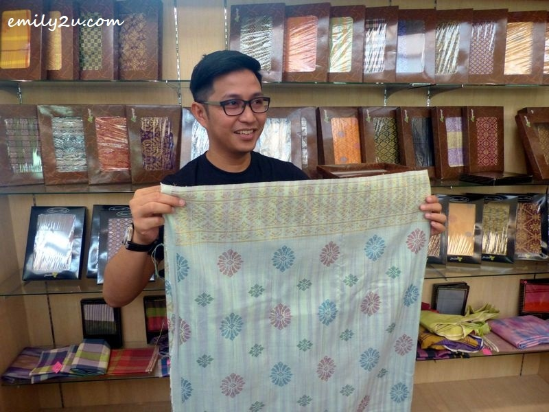 a visitor, Nuar Md Diah, checking out songket