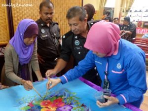 prison staff demonstrate the painting of batik