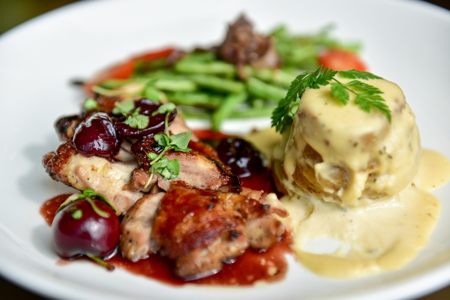 main course: black cherry roasted chicken, fresh black cherries, rosemary essence, seared cherry tomatoes with truffle scalloped potatoes-smoked gouda, chervil, and haricot verts lyonnaise - red onions, fresh thyme and nutmeg