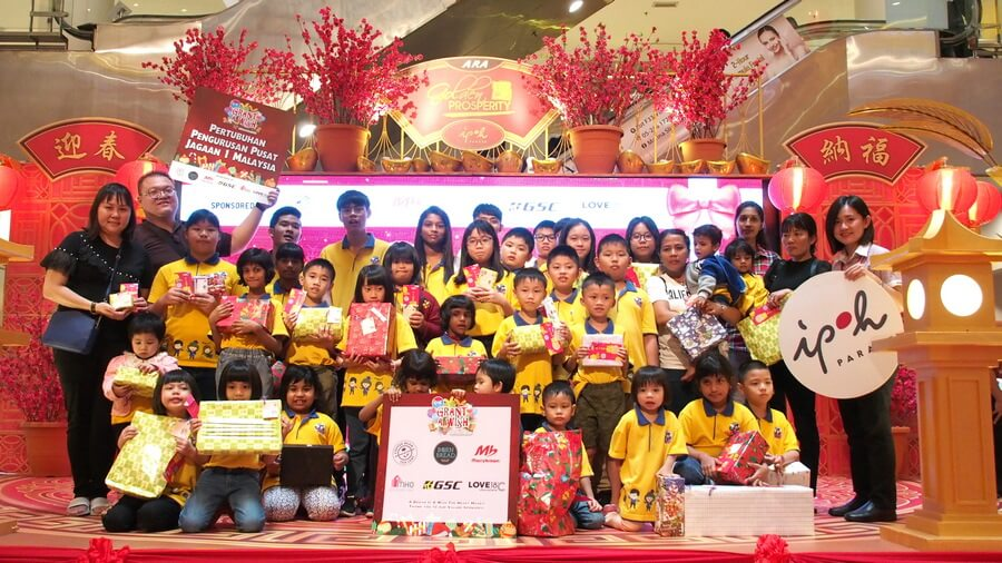 Children from Pertubuhan Pengurusan Pusat Jagaan 1 Malaysia in a group photo with the representative from Ipoh Parade, Surekha (3rd from right, back row) and Senior Restaurant Manager for Marrybrown, Chew Hui Xin (1st from right, standing).