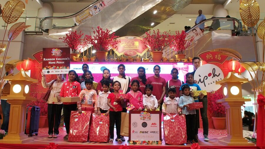 Children from Rainbow Children's Home Perak pose with ArtWatch owner, Low Kwee Mee (1st from right, standing), after receiving their gifts.