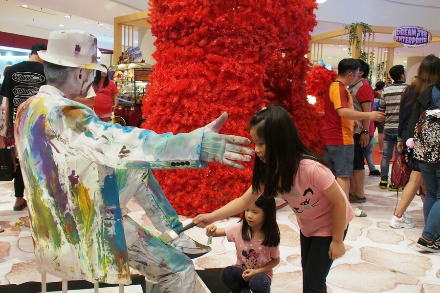 Children paint Blanko The White Statue with splashing colours.