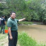 Mohd. Zulfadli Bin Zainor points at the pond where the false gharials live