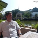 sitting by the Malacca River with the water wheel behind