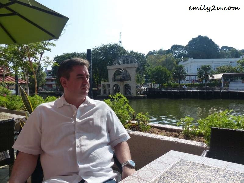 sitting by the Melaka River with the water wheel behind