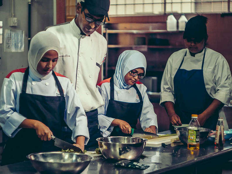 some of the students in kitchen practical under the watchful eye of their lecturer