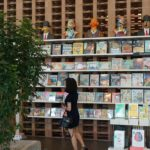 A customer browsing through the variety of genres available at BookXcess @ Wolf House