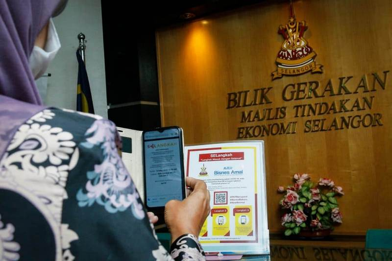 A government officer scans the QR code to use the mobile application SELangkah (Langkah Masuk Dengan Selamat) at Bangunan SUK Shah Alam.