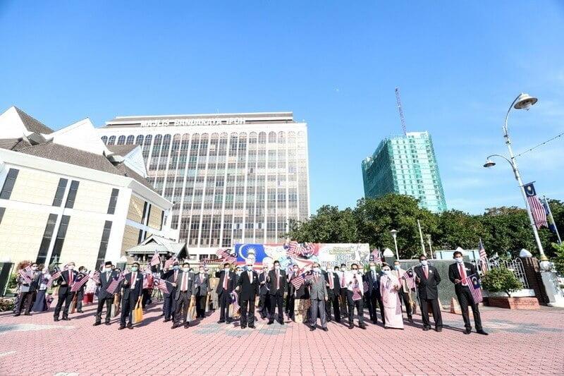 Ipoh City Mayor Dato' Rumaizi Baharin (in grey suit) leads in raising the Jalur Gemilang