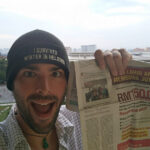 Holding up the first newspaper article after Freals tweet went viral