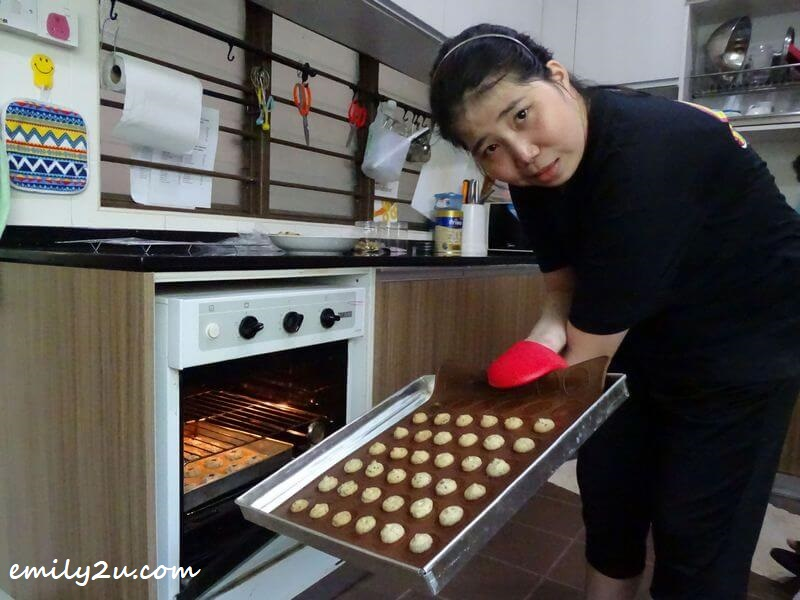 Keen places a tray of cookies in the oven