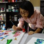 Jamila concentrating on her painting