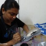 a deaf and mute worker busy painting shoes